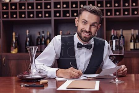 Photo pour Jeune bel homme sommelier dégustation de vin rouge dans la cave - image libre de droit