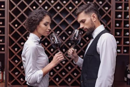 Photo for Two sommeliers, male and female tasting red wine in cellar - Royalty Free Image