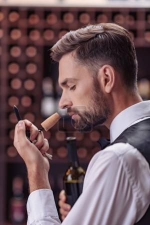 Photo pour Gros plan du sommelier professionnel examinant l'odeur du bouchon de vin dans la cave - image libre de droit