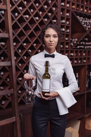 Photo for Portrait of young beautiful woman sommelier standing with bottle of wine and glass in cellar - Royalty Free Image