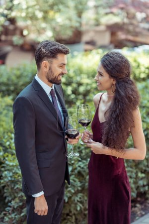 Photo for Happy young coupe standing with red wine in garden - Royalty Free Image
