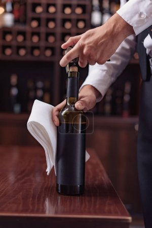 waiter opening wine bottle