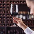 Young handsome man sommelier tasting red wine in c...