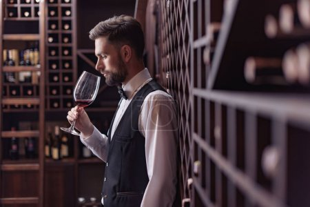 Photo pour Jeune bel homme sommelier dégustation de vin rouge dans la cave à vin - image libre de droit