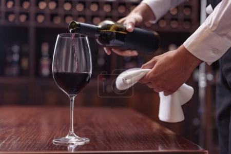 Photo for Cropped view sommelier pouring red wine from bottle into glass at table in cellar - Royalty Free Image