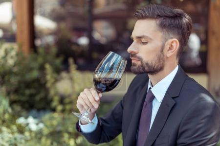 Photo pour Gros plan portrait d'un bel homme sommelier dégustant un verre de vin rouge, axé sur le vin - image libre de droit