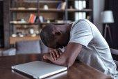 overworked man sleeping near laptop