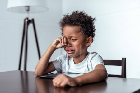 boy crying while sitting with tablet