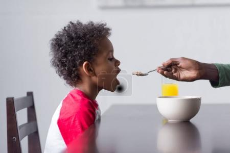 father feeding his son with breakfast
