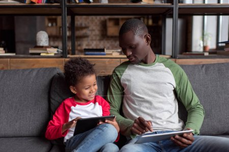 father and son using tablets