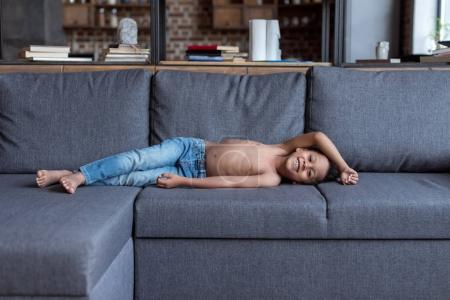 shirtless little kid playing on sofa