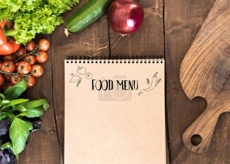 Photo for Overhead view of raw vegetables, chopping board and notepad on wooden table. Food composition background - Royalty Free Image