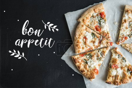 Photo pour Vue de dessus de pizza italienne traditionnelle tranchée sur parchemin sur surface sombre - image libre de droit