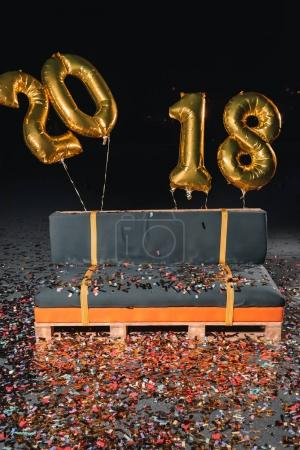 couch with confetti and new year balloons