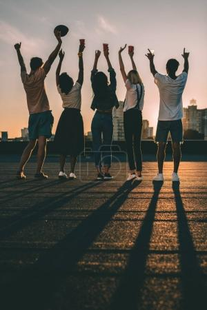 Photo for Silhouettes of group of happy friends on roof at sunset - Royalty Free Image
