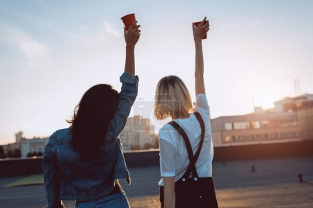 Photo for Women raising hands with plastic cups on rooftop - Royalty Free Image