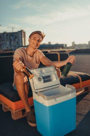 Photo pour Beau jeune homme sortant des bouteilles de bière du réfrigérateur portable - image libre de droit