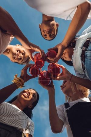 Foto de Vista inferior de los amigos tintineo vasos de plástico con alcohol al aire libre - Imagen libre de derechos