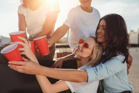 friends clinking with plastic cups