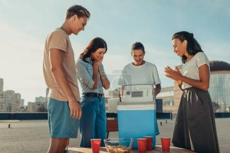 friends looking at portable fridge