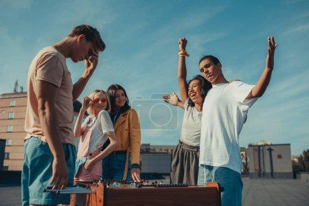 Photo pour Groupe de jeunes amis à jouer baby-foot sur toit - image libre de droit