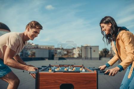 Photo for Happy couple playing table football on roof - Royalty Free Image