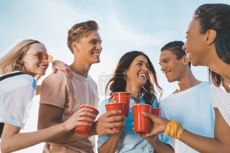 Photo pour Amis souriants cliquetis verres en plastique avec de l'alcool à l'extérieur - image libre de droit