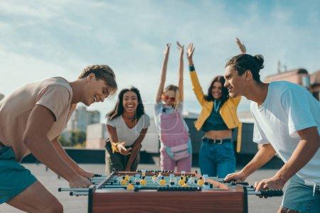 Photo pour Groupe de jeunes amis heureux jouant au baby-foot sur le toit - image libre de droit