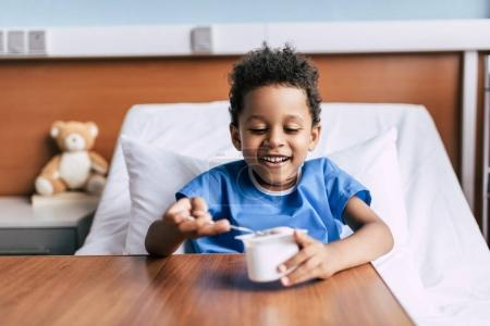 african american boy eating yogurt