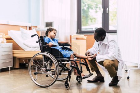 Photo for Side view of african american doctor examining foot of disabled patient in wheelchair in clinic - Royalty Free Image