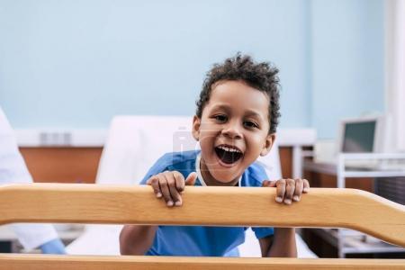 Photo pour Portrait de heureux garçon afro-américain regardant la caméra à l'hôpital - image libre de droit