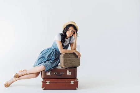 tired woman sitting on luggage
