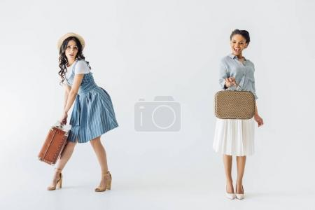 Photo for Multiethnic women in retro clothing with luggage in hands isolated on grey - Royalty Free Image