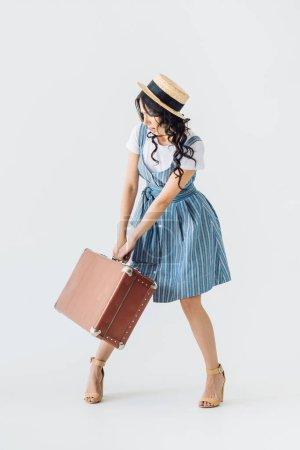 Photo pour Femme en vêtements de style rétro tenant lourde valise isolé sur fond gris - image libre de droit