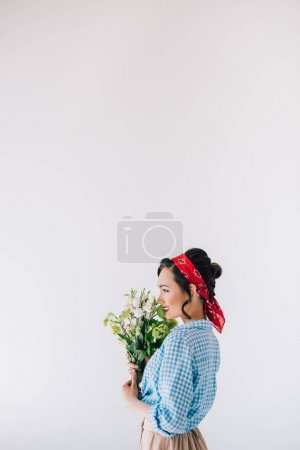 Photo for Side view of smiling asian woman in retro style clothing with bouquet of flowers isolated on grey - Royalty Free Image