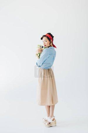 Photo pour Femme asiatique à la mode dans des vêtements rétro avec bouquet de fleurs isolé sur fond gris - image libre de droit