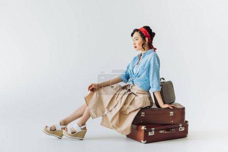 asian woman sitting on luggage