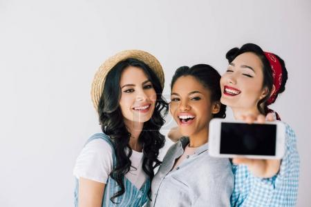 Photo for Multicultural happy women taking selfie on smartphone together isolated on grey - Royalty Free Image