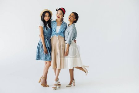 Stylish multicultural women in retro clothing posi...