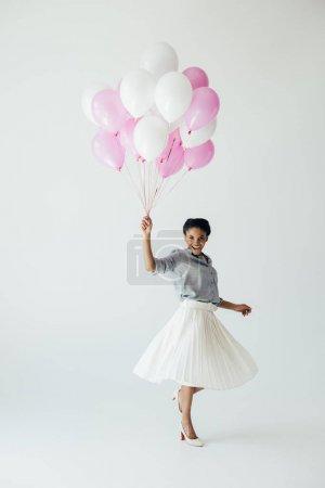 Photo pour Heureuse jeune femme afro-américaine tenant le bouquet de ballons isolé sur fond gris - image libre de droit