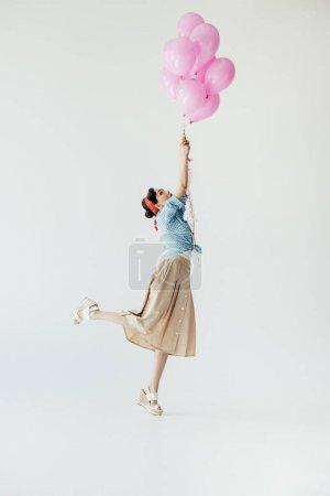 Photo pour Vue latérale de la belle femme asiatique dans les vêtements de style rétro tenant des ballons isolés sur fond gris - image libre de droit