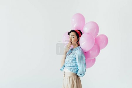 Photo for Side view of emotional asian woman holding balloons behind back isolated on grey - Royalty Free Image