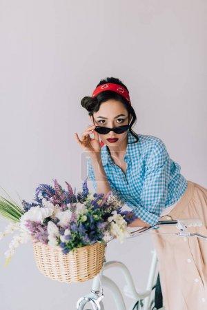 Photo pour Femme asiatique chic dans les vêtements rétro et lunettes de soleil se penchant sur le vélo et regardant la caméra isolée sur fond gris - image libre de droit