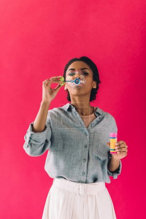 african american woman blowing soap bubbles