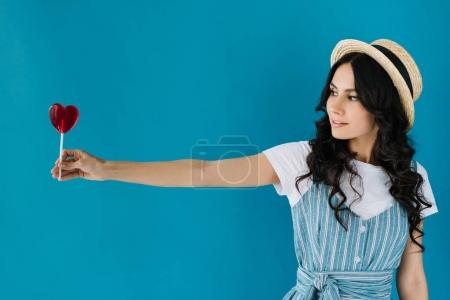 Photo for Portrait of beautiful woman looking at lollipop in hand isolated on blue - Royalty Free Image