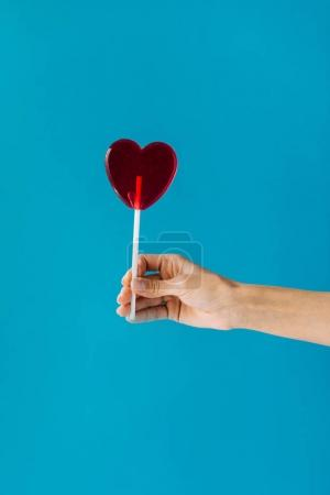 Photo for Cropped shot of female hand holding heart shaped lollipop isolated on blue - Royalty Free Image