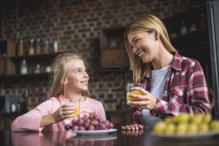 Photo for Cheerful mother and daughter having breakfast together at home - Royalty Free Image