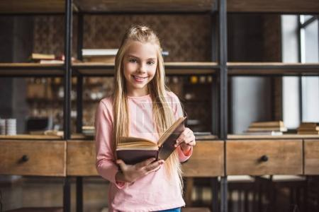 Photo for Portrait of smiling little girl with book in hands looking at camera at home - Royalty Free Image