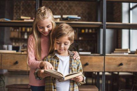 Photo pour Portrait d'adorables enfants lisant ensemble un livre à la maison - image libre de droit