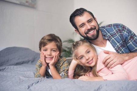 Photo pour Portrait de père heureux et de petits enfants se reposant sur le lit ensemble à la maison - image libre de droit